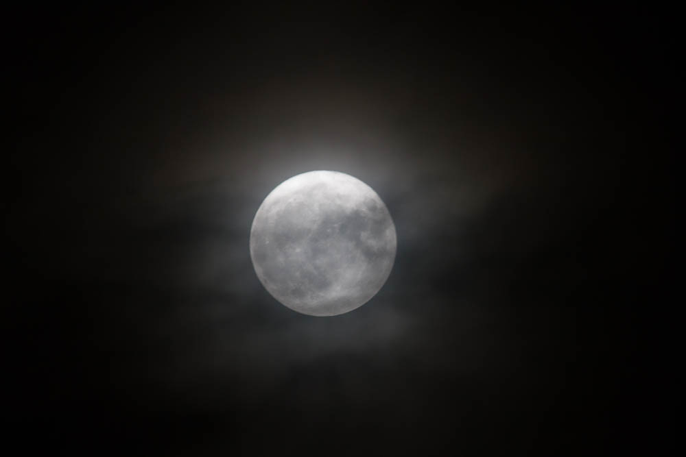 8 pm moon peeps through the clouds
